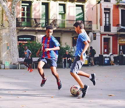 kids playing football on a city square in Portugal